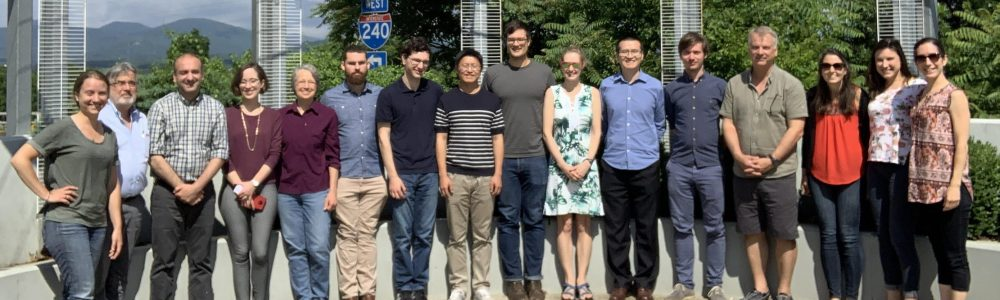 A photo of the research group standing outside the location of their 2019 workshop.